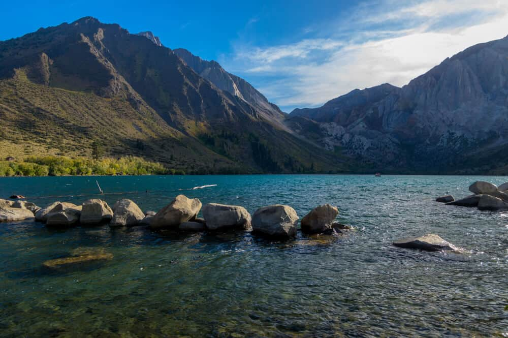The beautiful turquoise waters of Convict Lake with many boulders in the water with mountains rising above the lake.