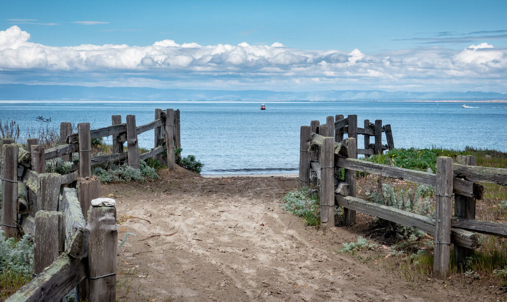 A sandy path lined by wooden fence leads to Del Monte Beach, along the central California Pacific Coast in Monterey.