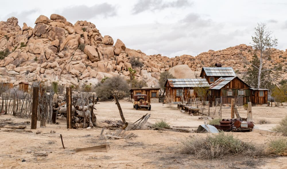 A dilapidated wood and tin roof mining house in the middle of the Joshua Tree landscape, a popular hiking destination also good for history lovers