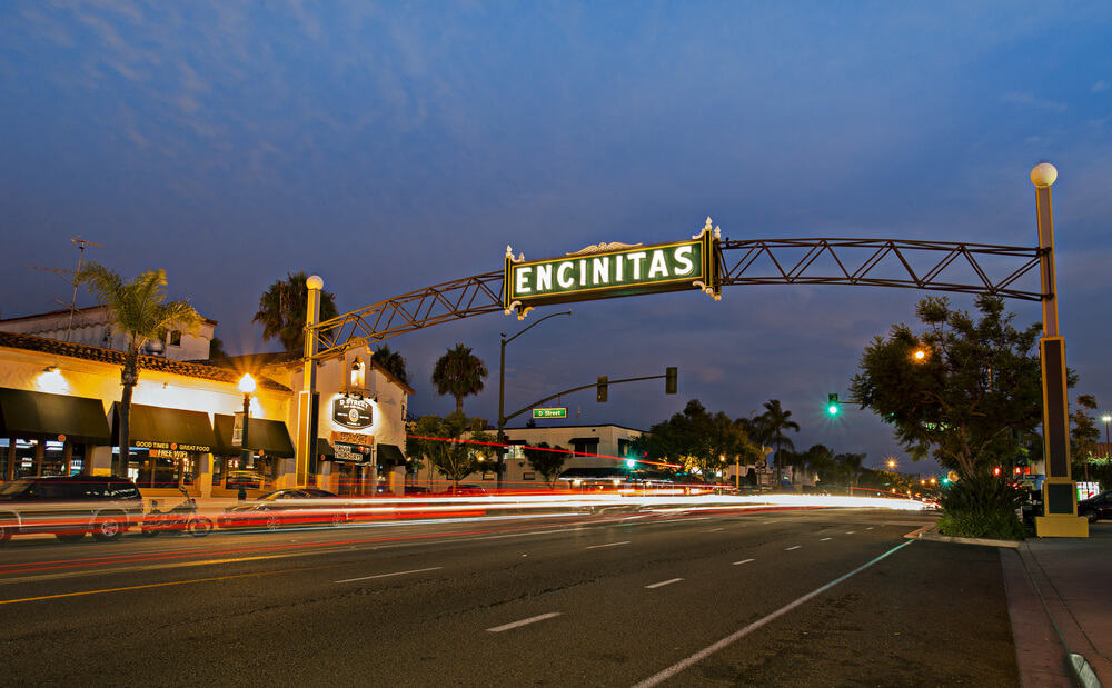 nighttime view of the encinitas sign with light trails from passing cars