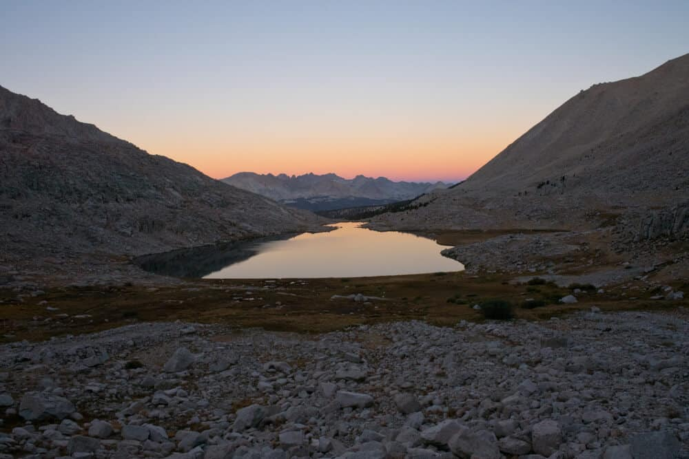Sunrise over Guitar Lake from the climb of Mount Whitney on the John Muir Trail in Kings Canyon National Park in California. Orange and pink sky and a small lake in the mountains shaped like a guitar body.