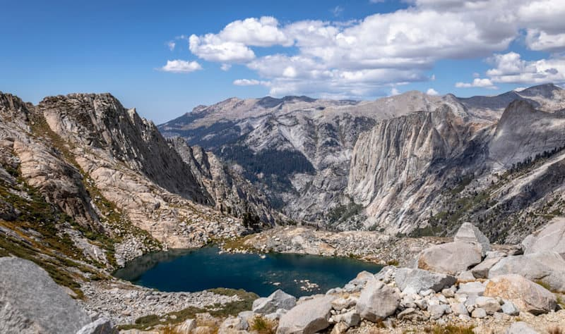 a still blue lake at the middle of a glacier basin between high sierra peaks