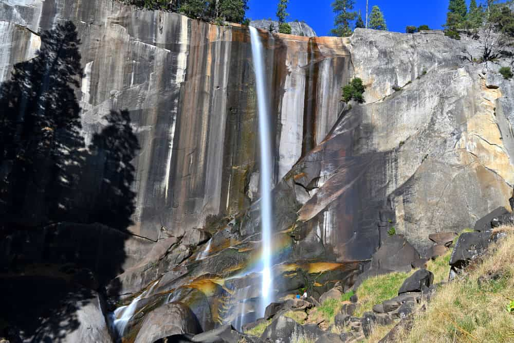 A narrow stream of a waterfall cascading over a granite cliff, creating a rainbow at the bottom in Yosemite National Park