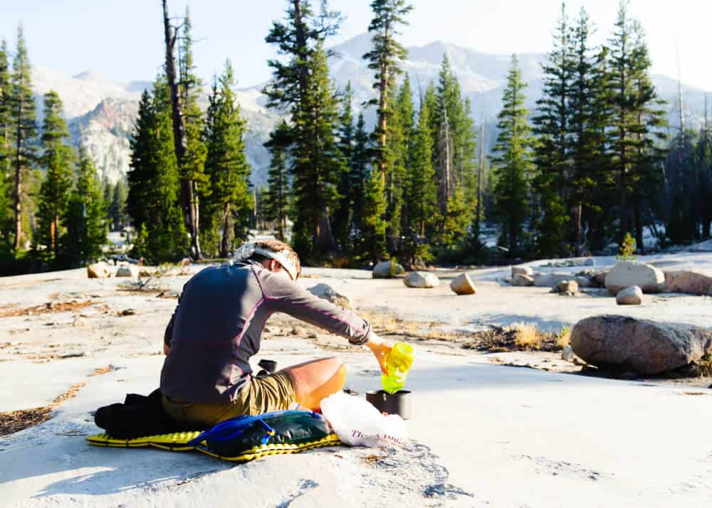 Hiker filling a small cooking pot with water to boil from a container sitting on a pad with mountains in the distance