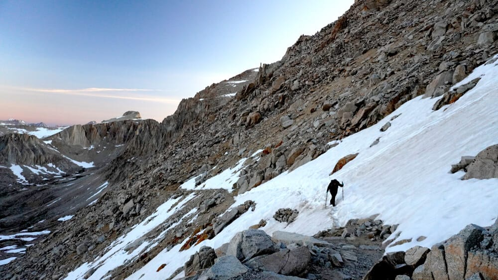 hiker on snow on a mountain face climbing a high sierra pass