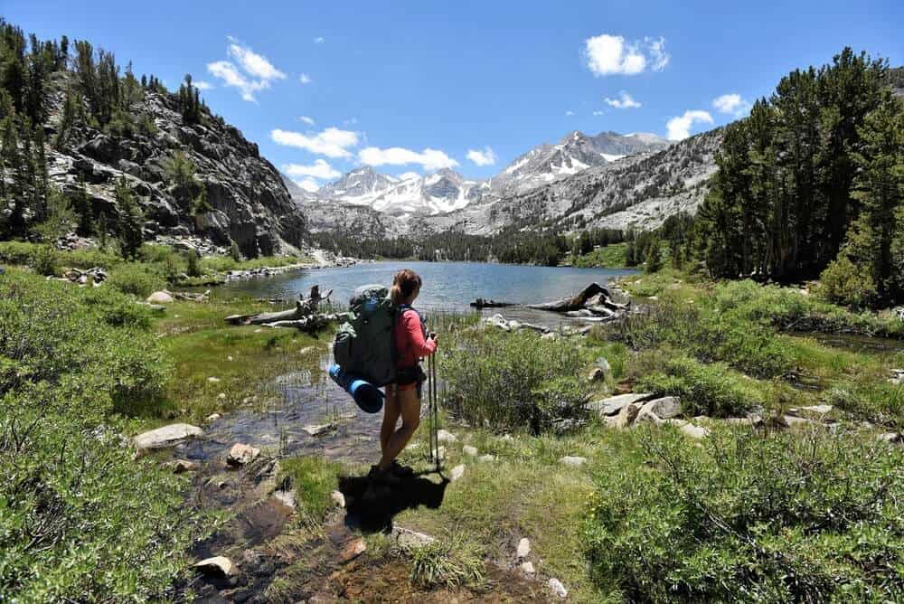 Female hiker in shorts and pink or red T-shirt hiking the John Muir Trail, looking out with trekking poles onto a lake surrounded by mountains.