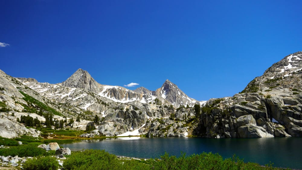 Clear day in the Sierras on the John Muir Trail at an alpine lake with granite mountain peaks