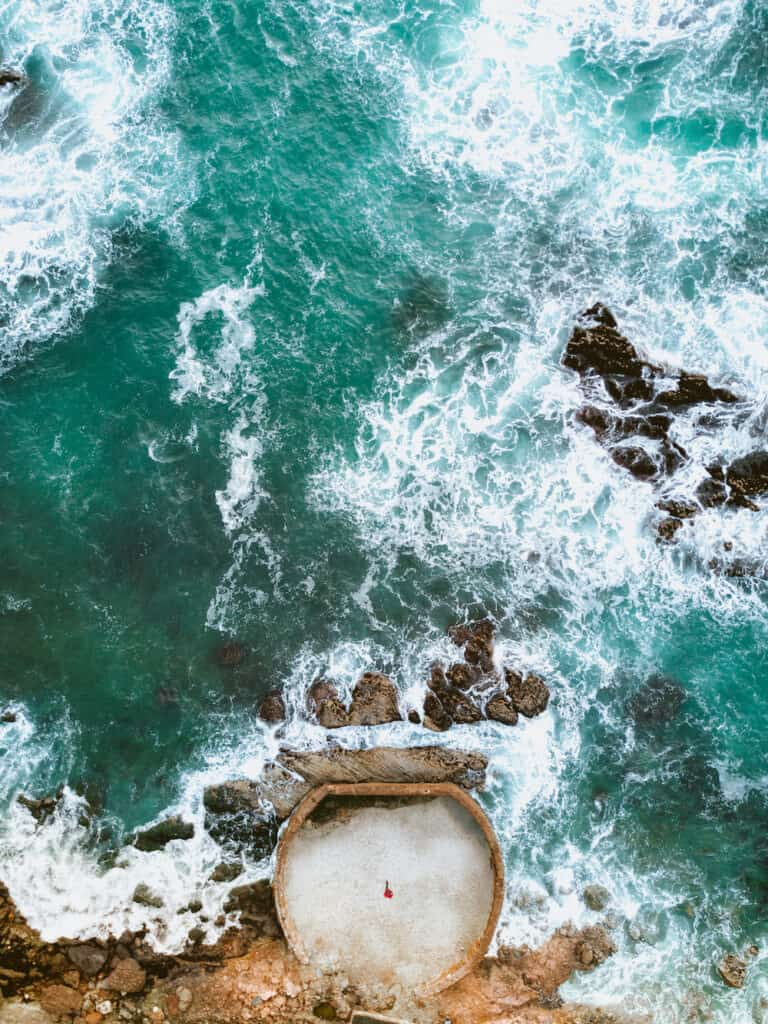 Aerial photo of a birds eye view of crashing turquoise waves and a small figure in a cement pool by the side of the water.