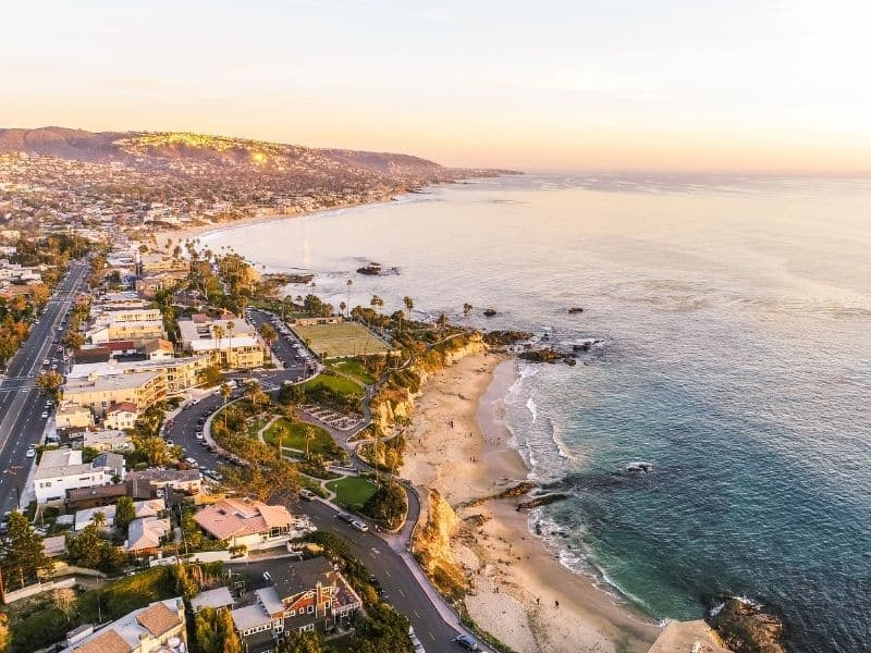 Sunset over Laguna Beach's waterfront and beachfront with a view of roads and the Pacific Coast Highway