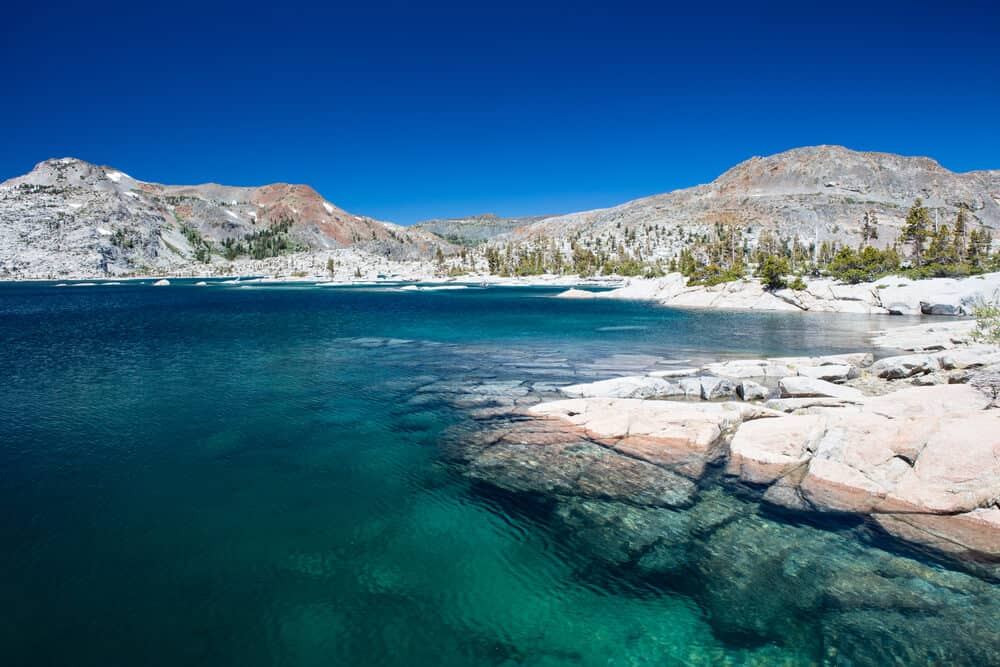 Perfectly clear water in an alpine lake in the Sierras surrounded by grey mountain rock