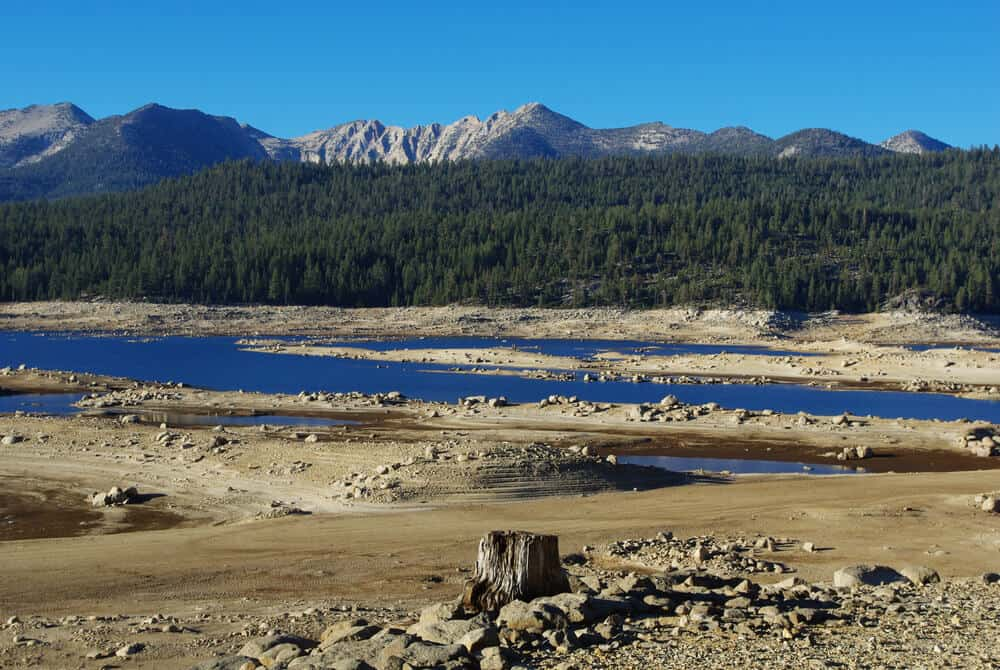Landscape surrounding Edison Lake - blue water and trees and granite mountains in the distance.