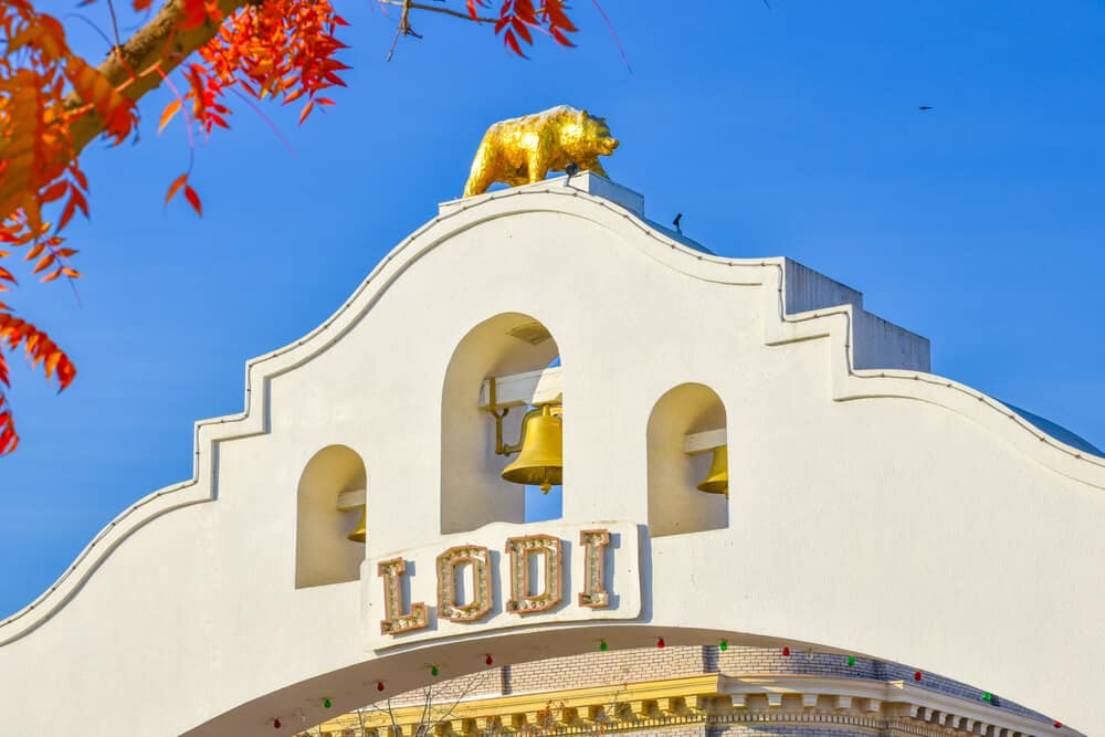 """White arch that reads """"LODI"""" with a gold bell and a golden bear atop, a California state symbol"""