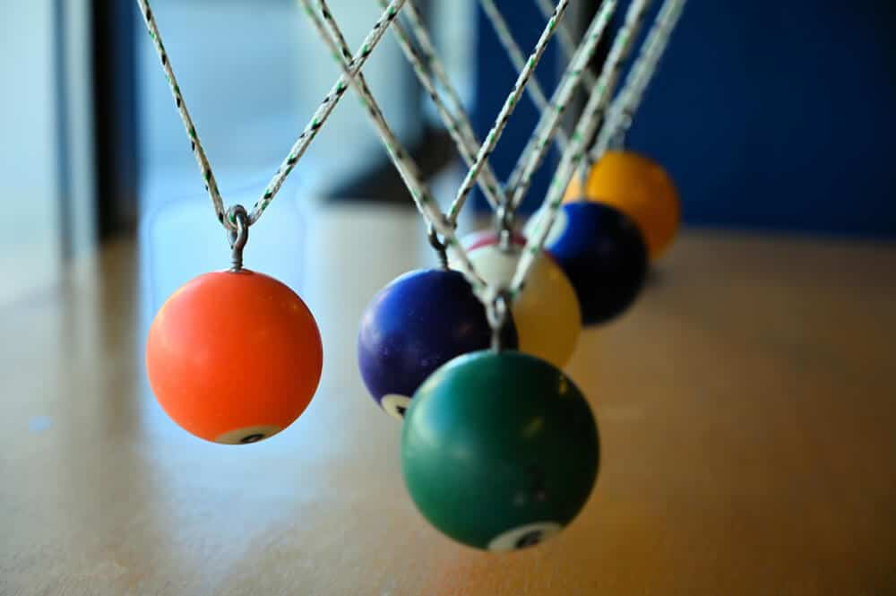 Billiard balls suspended on string to form a pendulum, shown at the science museum in Lodi
