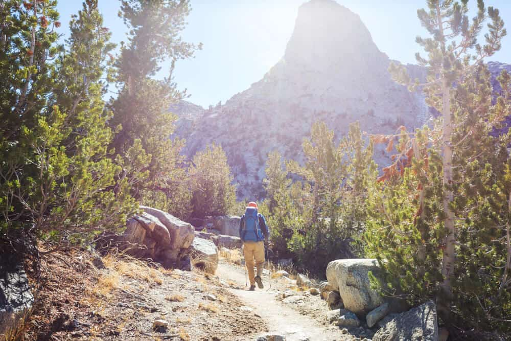 man walking on trail in high sierra with large granite cliff faces around him
