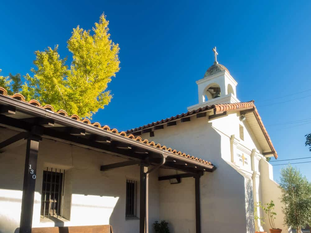 white church building with bell tower and cross and adobe roof in santa cruz