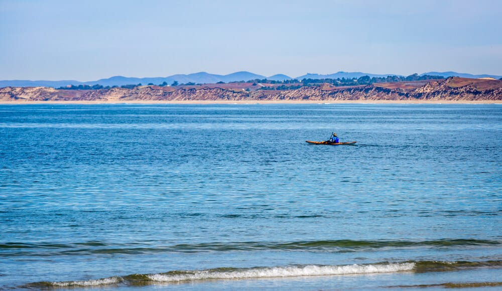 Lone kayaker paddling out to the bay near Monterey, California