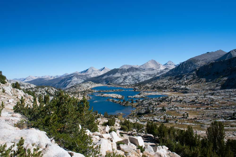 Muir Lake along the John Muir Trail: a small emerald-blue lake surrounded by rugged landscape, green trees and mountain peaks