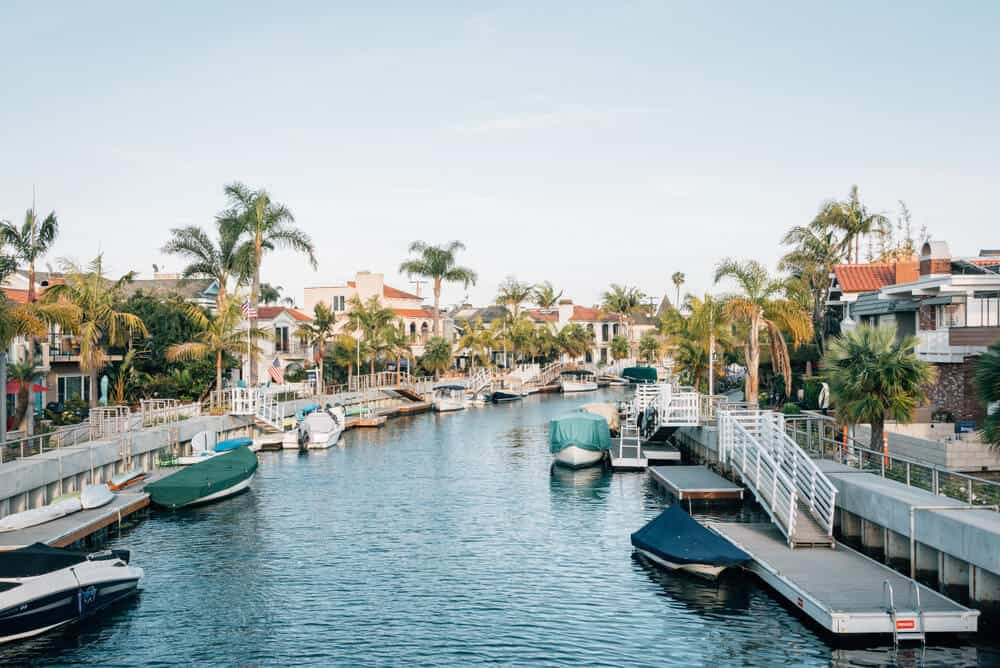 covered boats and houses on a canal in the  pretty naples neighborhood of long beach California with palm trees everywhere