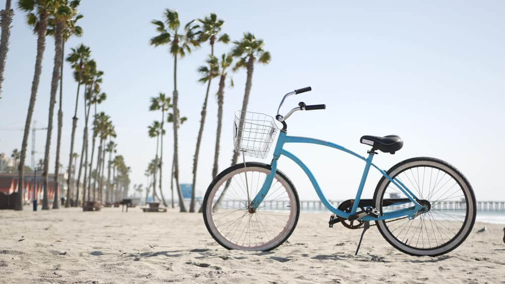 Blue bicycle, cruiser bike by sandy ocean beach, pacific coast near Oceanside pier. Vintage cycle, tropical palm trees, lifeguard tower watchtower hut