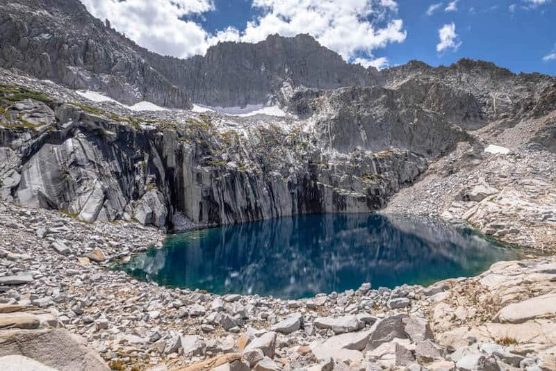 a mirror-lake still alpine lake surrounded by basalt columns and rocks