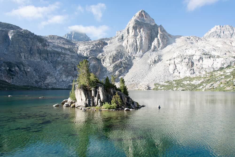 Rae Lakes: a lake with a small rock islet in the middle surrounded by turquoise waters and mountain peaks