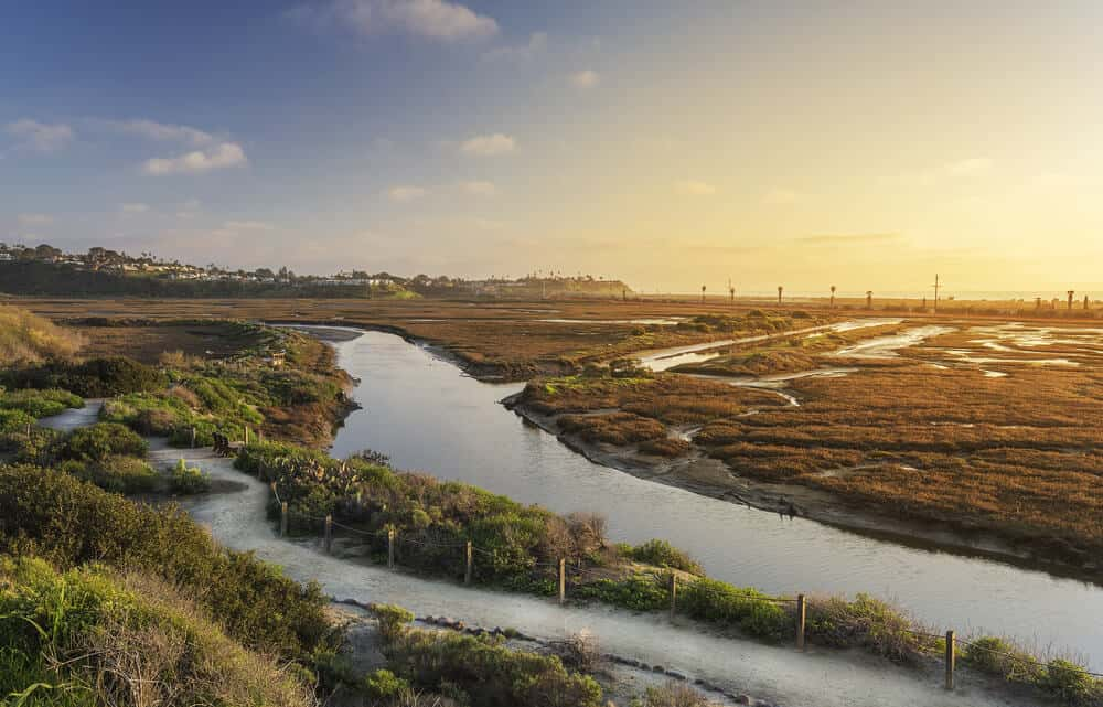 sunset over the san elijo lagoon - wetlands interspersed with water along a coastal path for hiking in encinitas