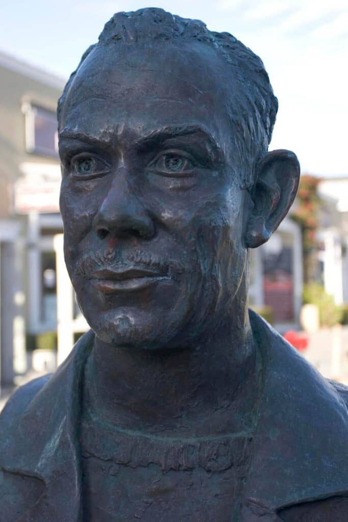 Statue showing John Steinbeck in Monterey with buildings behind it