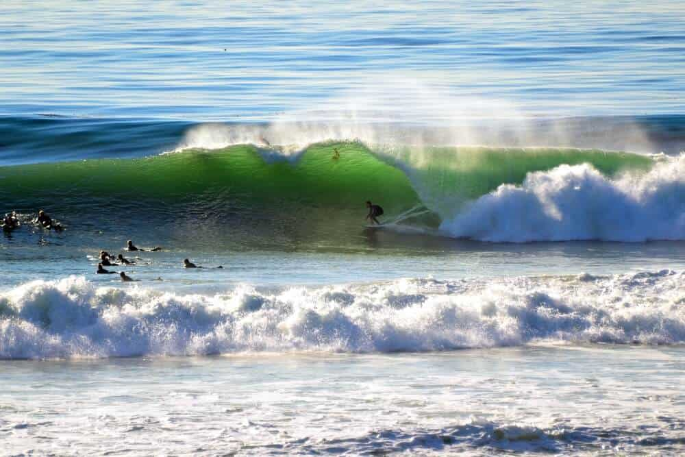 many surfers gathering on the waves of swamis surf breaks, a popular thing to do in encinitas