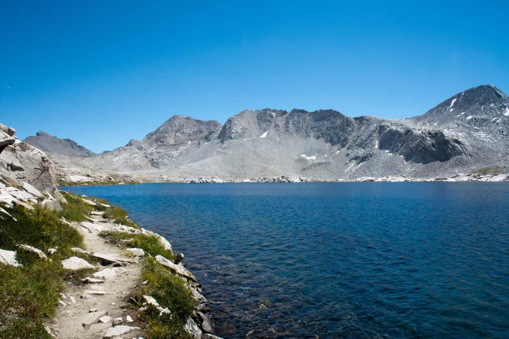 The edge of Wanda Lake, a deep sapphire blue lake in Kings Canyon National Park, part of the John Muir Trail hike