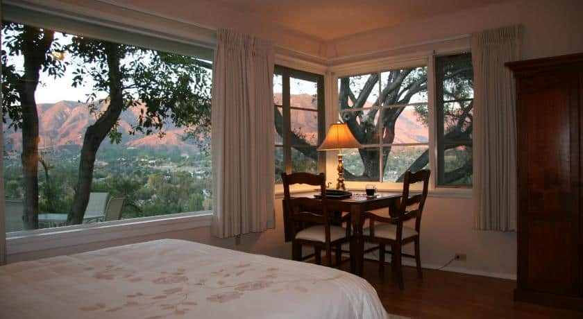 a room with a small table in the corner with a gorgeous view of the mountains at sunset