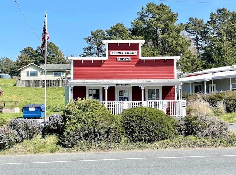 tiny red post office with american flag pole