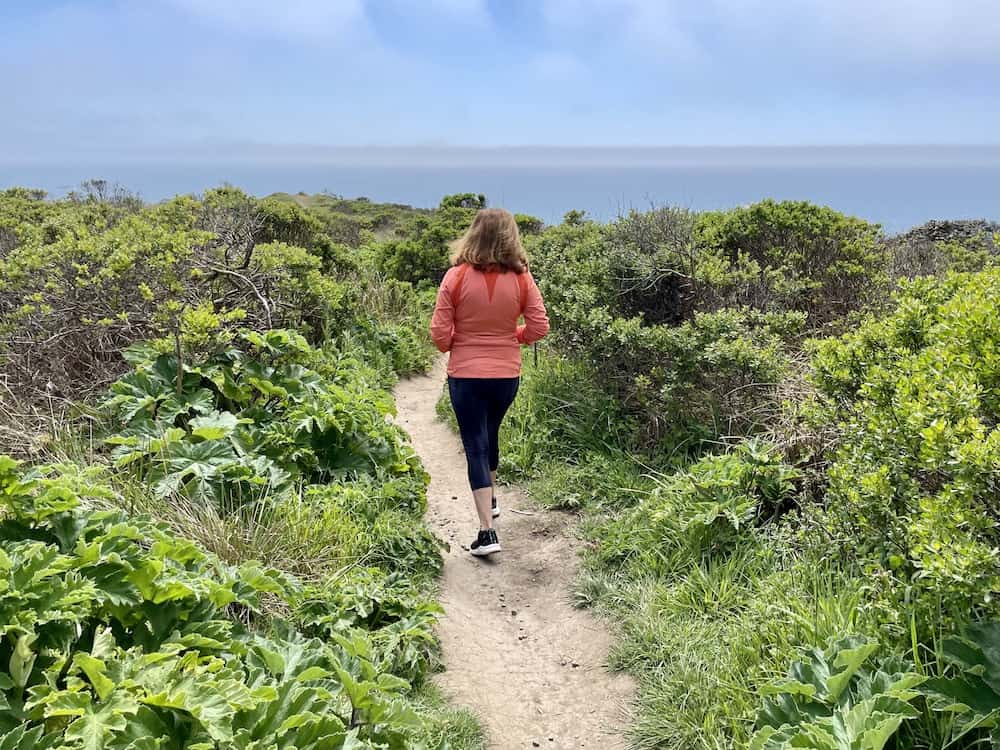 allison's mother wearing a orange jacket and leggings walking on the kortum trail in jenner