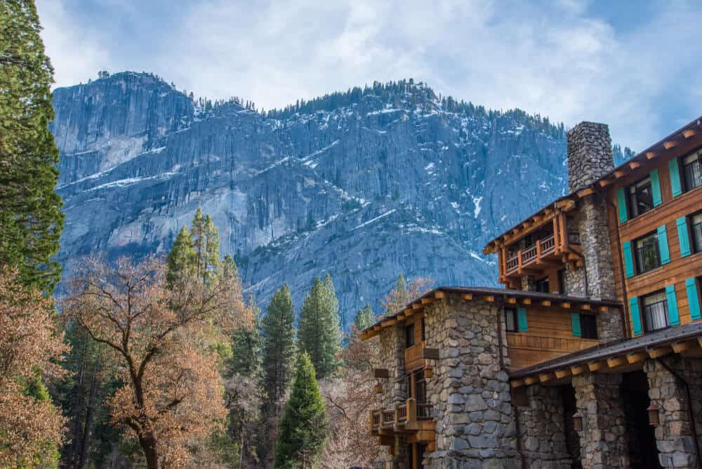 the famous stone and wood ahwahnee hotel in Yosemite, next to autumn trees, evergreens, and a mountain backdrop