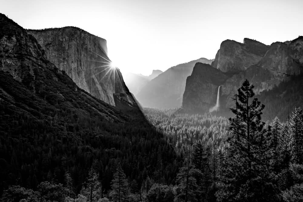 black and white view over tunnel view with a waterfall and sunbeam done in the ansel adams style