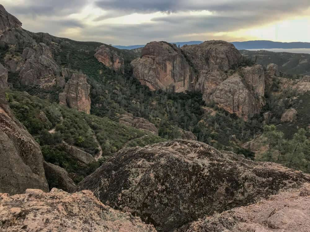 Sunset over Pinnacles National Park from an overlook with large red rocks and green trees