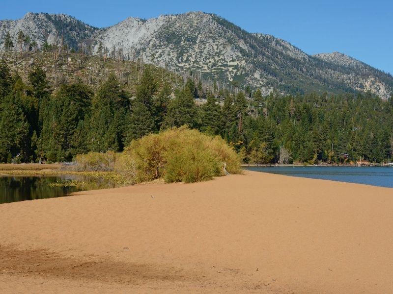 orange-brown sand of baldwin beach in lake tahoe near a meadow and basin or shallow water
