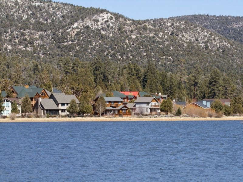 lake shore with houses on the edge of the lake with large mountains behind the houses.