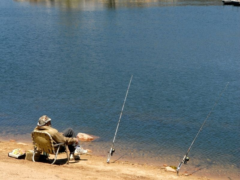 man sitting on chair with two fishing poles at big bear lake in summer