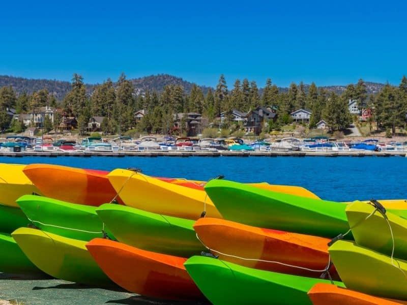 a pile of kayaks by the bank of lake big bear