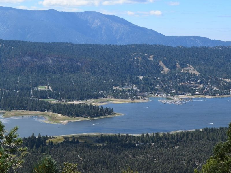 view of big bear lake in summer surrounded by trees on a hiking trail on the mountain above the lake