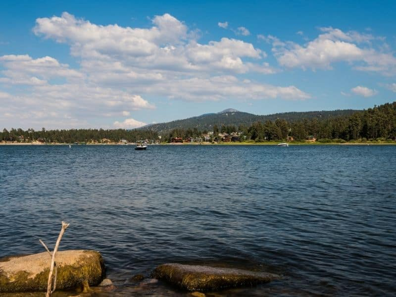 the calm waters of big bear lake in summer with two boats on the water on a partly cloudy day.