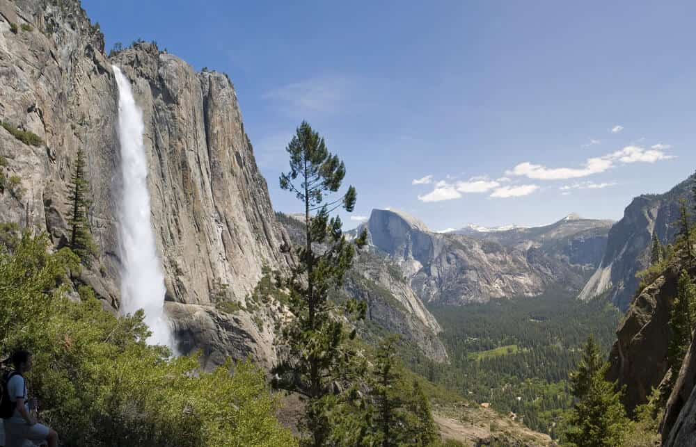 waterfall cascading over yosemite granite domes down into the valley below
