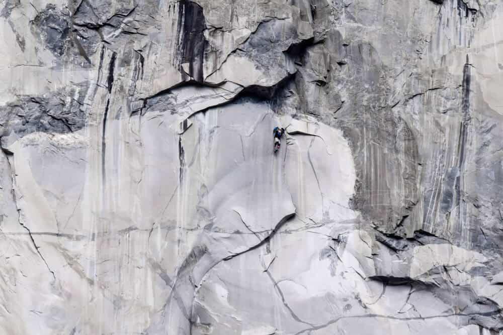 person climbing the granite face of el capitan rock in yosemite