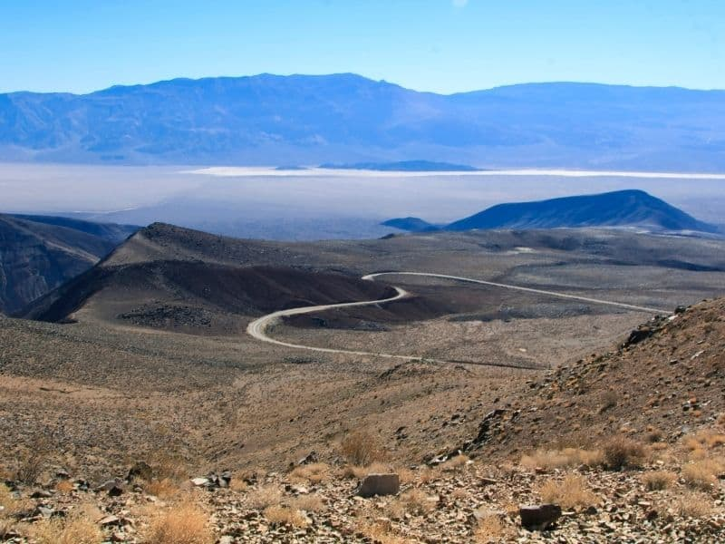 view of the death valley basin below with a curved road and salt flats in the distance