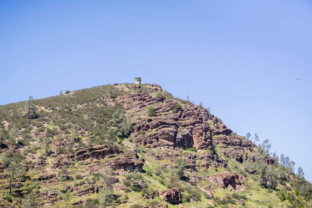 The fire tower atop North Chalone Peak in Pinnacles National Park, a mountain of reddish volcanic rock covered in desert-like greenery