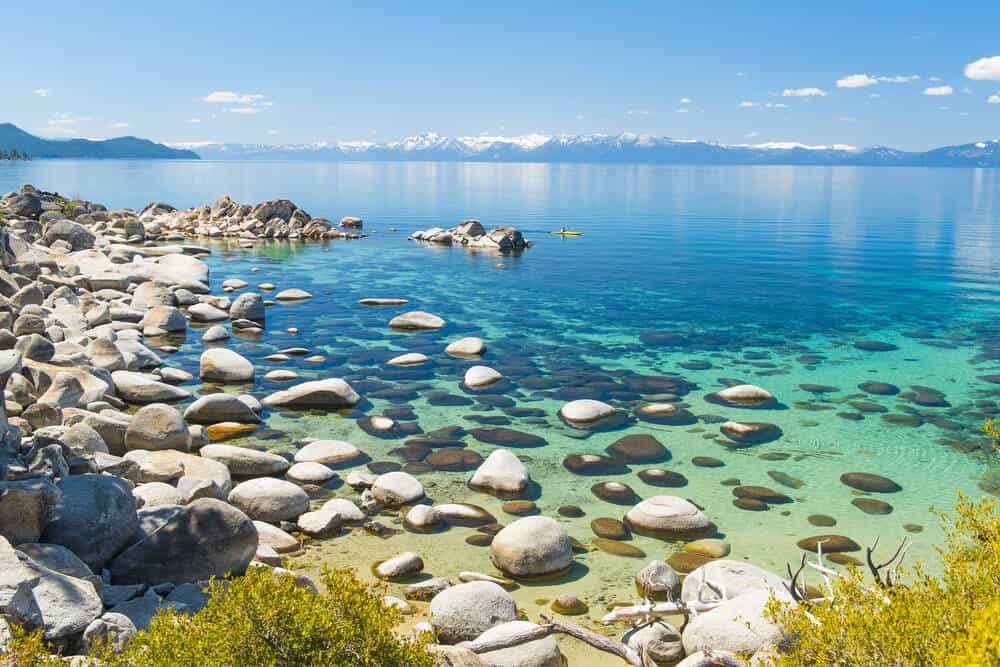 rock-strewn waters of lake beach at hidden beach near incline village in north tahoe beach. kayaker in the distance in blue-green waters