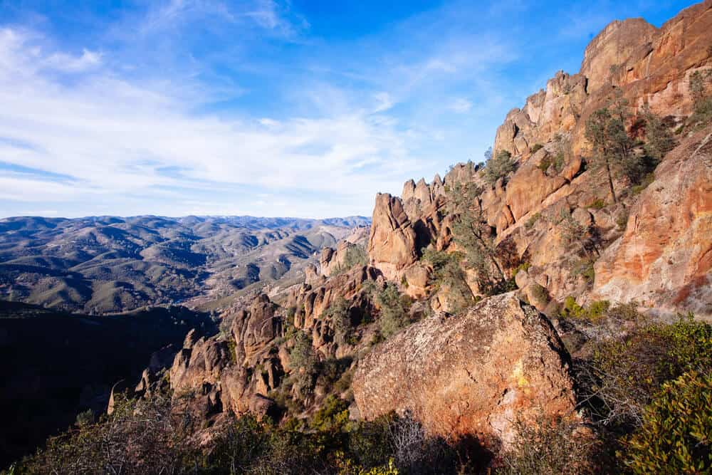 Reddish rocks and spires of Pinnacles National Park with smaller foothills way off in the distance from a high elevation
