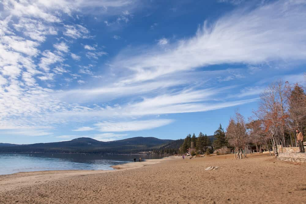 the sandy beach in tahoe in kings beach surrounded by fall trees and a cloudy sky with one person visible on the beach