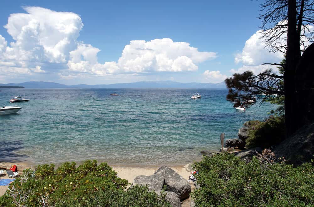 rocks on a sandy beach at lake tahoe with boats off in the distance and clouds on the horizon
