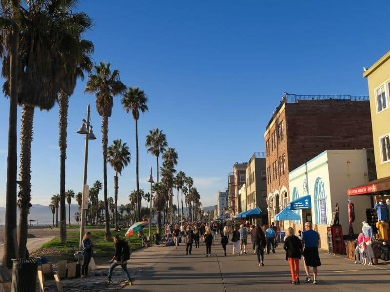 venice beach boardwalk with lots of people walking and watching